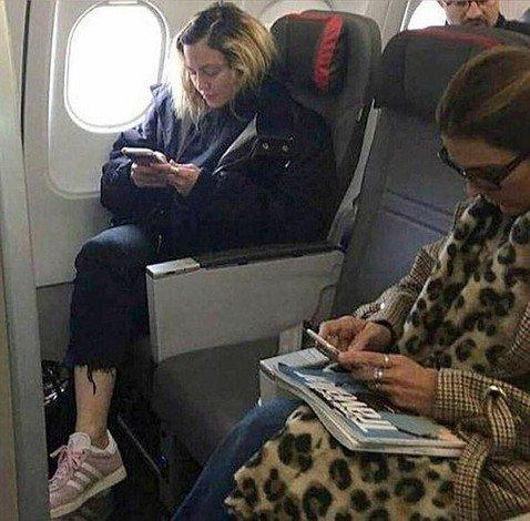 Мадонна без макияжа и укладки ничем не выделялась среди пассажиров эконом-класса